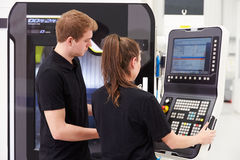 Two Young Engineers Operating CNC Machinery On Factory Floor stock photography