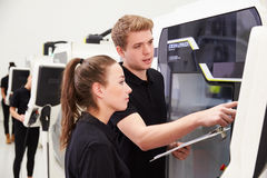 Two Young Engineers Operating CNC Machinery On Factory Floor Royalty Free Stock Image