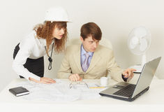 Two young engineers work over project on laptop Stock Photos
