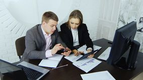 Two young enterprising business partners work on a tablet in a study on the background of a round window stock video footage