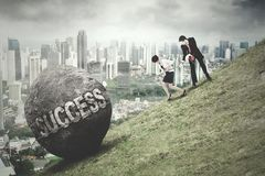 Entrepreneurs pull boulder with Success word Stock Images