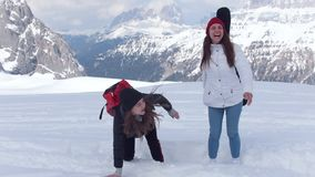 Two young excited women travelers happily jumping in the snow in Dolomites stock video