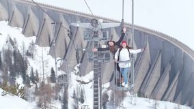 Two young excited women traveling in Dolomites. Lifting on a funicular stock footage