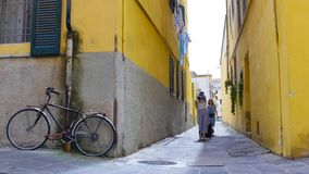 Two young excited women walking through the narrow yellow streets with luggage royalty free stock photography