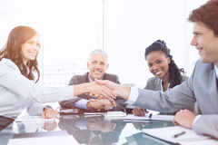 Two young executives shaking hands in front of their director and a colleague. Young smiling executives shaking hands in front of their manager and a colleague Royalty Free Stock Photos