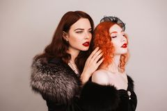 Two young fabulous lesbian girls with curly long hair in black dress on dark background. A beautiful retro woman with pale skin an. Two young fabulous lesbian stock image