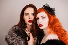 Two young fabulous lesbian girls with curly long hair in black dress on dark background. A beautiful retro woman with pale skin an. Two young fabulous lesbian Royalty Free Stock Photos