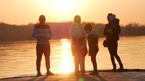 Two young families with children having fun near the river at sunset. Young active people. Outdoors, lifestyle.