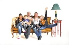 Two young families play the fool with a child sit on a sofa Stock Images