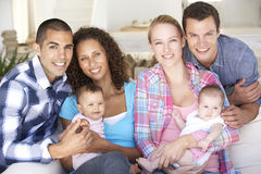 Two Young Family With Babies On Sofa At Home Stock Photo