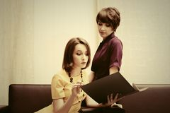 Two young fashion business women with a folder at office Stock Image