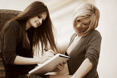 Two young fashion business women with notebook Royalty Free Stock Photography