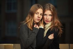 Two young fashion girls in black pullover and scarf in night city street. Stylish female teen models outdoor Royalty Free Stock Photography