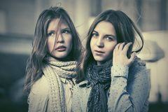 Two young fashion girls in a city street Royalty Free Stock Images