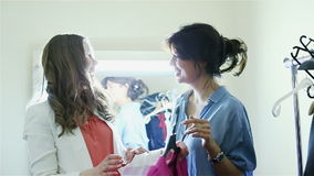 Two young fashion girls are at the clothing store. Happy girlfriends trying on a pink dress. Beautiful girl laughing in the store dressing room stock video