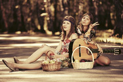 Two young fashion girls with fruit baskets sitting on the road Stock Images