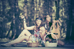 Two young fashion girls with fruit baskets in summer forest. Two happy young fashion girls with fruit baskets in summer forest Royalty Free Stock Photo