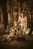 Two young fashion girls with guitar in a summer forest Royalty Free Stock Images