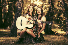 Two young fashion girls with guitar in a summer forest. Two happy young fashion girls with guitar in a summer forest Royalty Free Stock Image