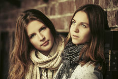 Two young fashion girls next to brick wall Royalty Free Stock Images