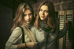 Two young fashion girls next to brick wall Stock Photos