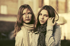 Two young fashion girls walking in a city street Royalty Free Stock Photo