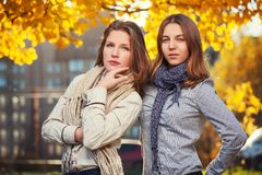 Two young fashion girls in white shirt and scarf walking in city street Stock Image