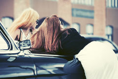 Two young fashion women leaning on vintage car in city street. Two young fashion women in sunglasses leaning on vintage car in city street Royalty Free Stock Photos