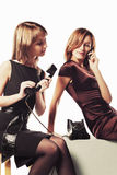 Two young fashion women with mobile and retro phone Royalty Free Stock Photography