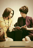 Two young fashion women reading a magazine in showroom. Two young fashion women reading a magazine sitting on couch in showroom Stock Images