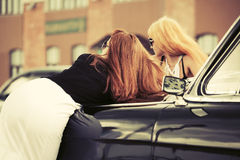 Two young fashion women by retro car Royalty Free Stock Images