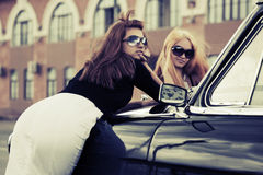Two young fashion women by retro car Royalty Free Stock Photos