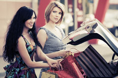Two young fashion women with shopping bags by car Stock Photography