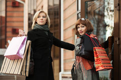 Two young fashion women with shopping bags at the mall door Royalty Free Stock Images