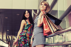 Two young fashion women with shopping bags in the mall Royalty Free Stock Photo