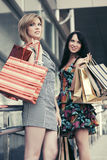 Two young fashion women with shopping bags in the mall Royalty Free Stock Image
