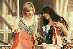 Two young fashion women with shopping bags in the mall Stock Image