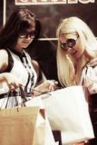 Two young fashion women with shopping bags at the mall Royalty Free Stock Photos