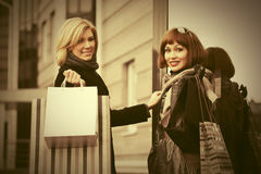 Two young fashion women with shopping bags next to mall door Stock Image