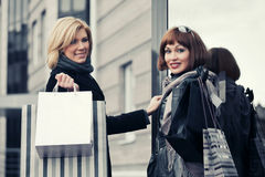 Two young fashion women with shopping bags next to mall door Royalty Free Stock Photo