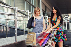 Two young fashion women with shopping cart Royalty Free Stock Photos