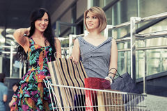 Two young fashion women with shopping cart in the mall Stock Photography