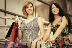 Two young fashion women with shopping cart in the mall Royalty Free Stock Images