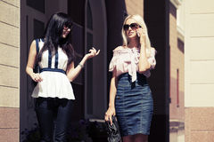 Two young fashion women walking on city street Royalty Free Stock Images