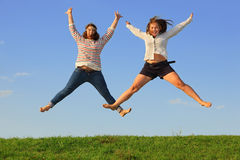 Two young fat girls jump at grass Stock Photos