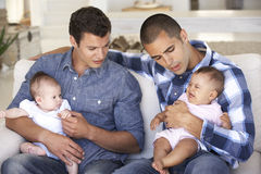 Two Young Fathers On Sofa At Home Royalty Free Stock Image