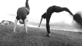 Two young female acrobat workout outdoors performing jumps. Close up stock footage