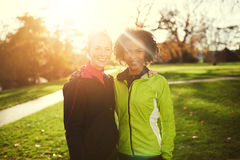 Two young female athletes hugging while standing in park Stock Photos