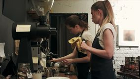 Two young female barista working in coffee shop, pareparing coffee stock footage