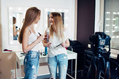 Two young female bloggers recording makeup tutorial on camera in beauty shop.  Royalty Free Stock Photography